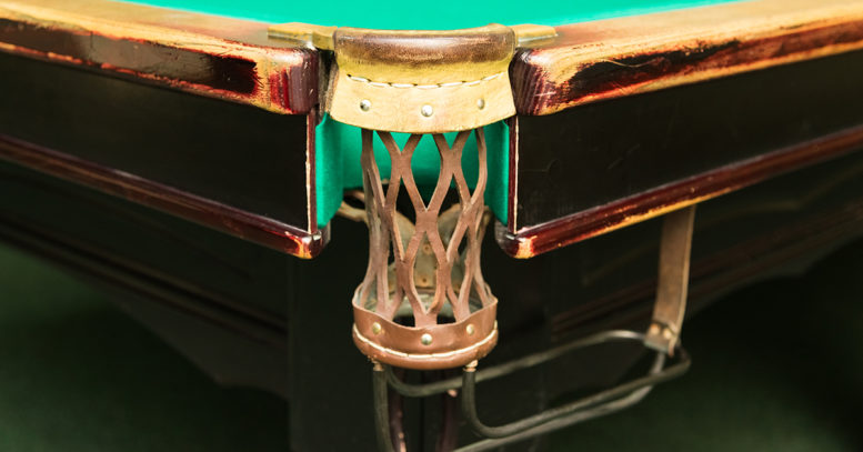 An empty pocket on an old billiard table
